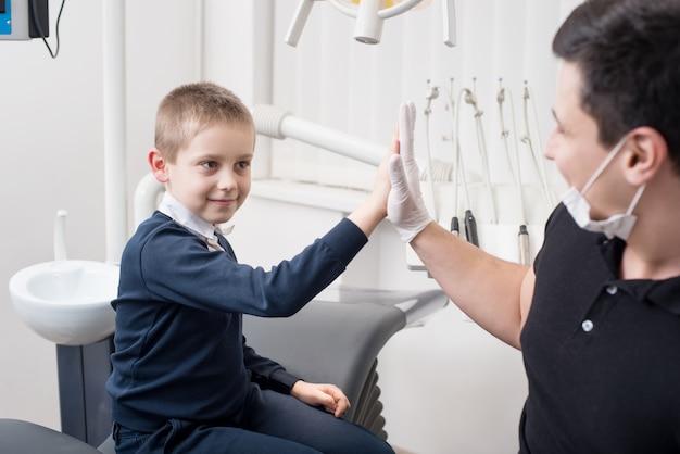 Kindertandarts geeft vijf jonge jongens, feliciteer de patiënt voor een succesvolle behandeling Premium Foto