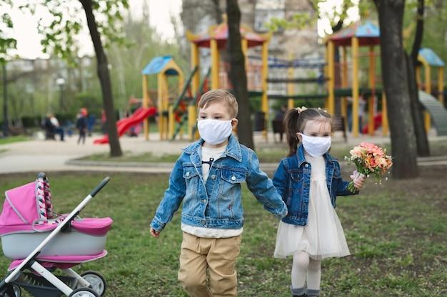 Kindjongen en meisje die in openlucht met de bescherming van het gezichtsmasker lopen. coronavirus (covid-19 Premium Foto