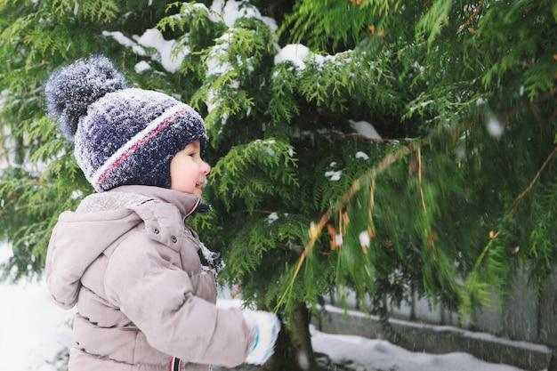 Kindjongen en sneeuw. winter tijd. Premium Foto