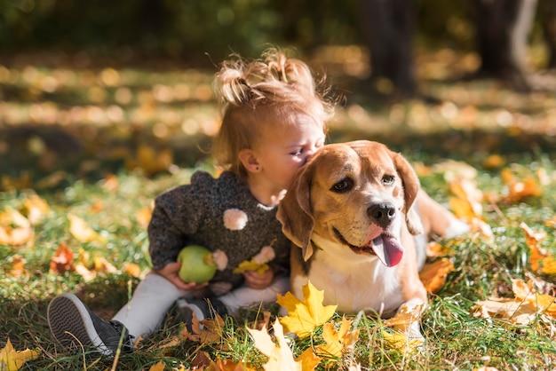 Kindmeisje die haar hondzitting in gras kussen bij bos Gratis Foto