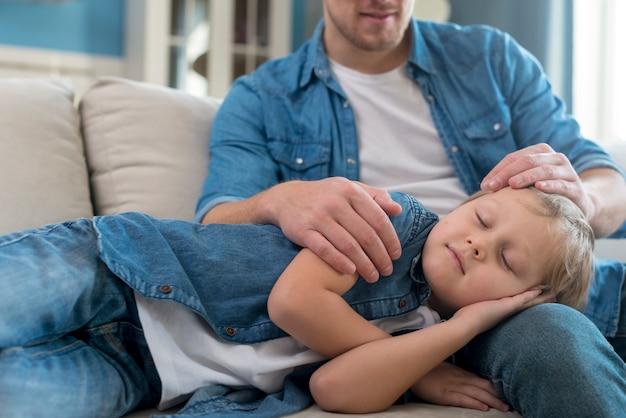 Kindslaap op vaders benen Gratis Foto