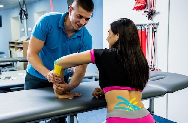 Kinesiotaping. fysiotherapeut die band toepassen op de rug van de jonge mooie vrouw Premium Foto