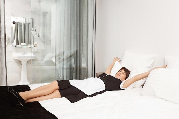 King size bed voor koningin. ontspannen en zorgeloos dienstmeisje liggend en strekkend op bed, opgelucht. maid besluit een dutje te doen na het schoonmaken van vuil in het appartement van haar werkgever terwijl hij aan het werk is Gratis Foto