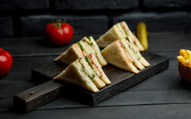 Kip club sandwich op een houten bord Gratis Foto