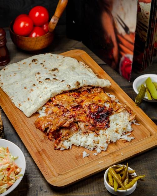 Kip doner met rijst op houten bord Gratis Foto