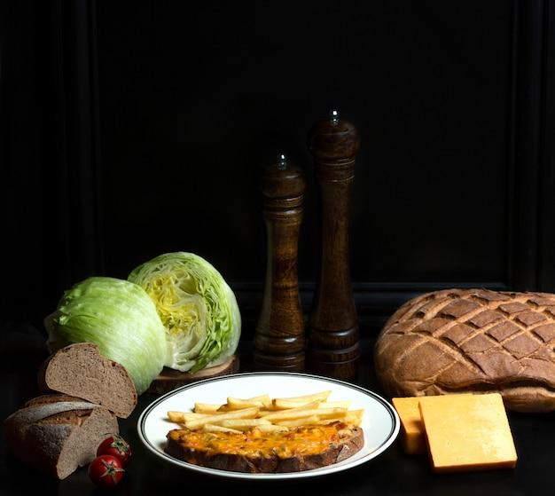 Kip en tomaten gegarneerd met geraspte kaas op brood en frietjes Gratis Foto
