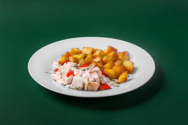 Kip, kalkoen met roomsaus en rode peper, gebakken aardappelen. op een witte plaat. groene achtergrond. zijaanzicht Premium Foto