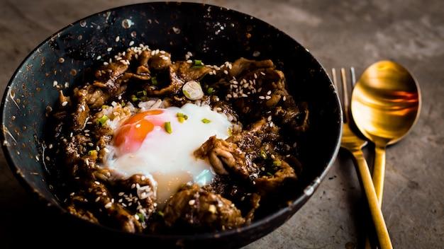 Kip met rijst, uien en broccoli op de tafel. horizontale weergave van bovenaf. japans eten rijst geserveerd met kip in teriyaki saus en ei Premium Foto