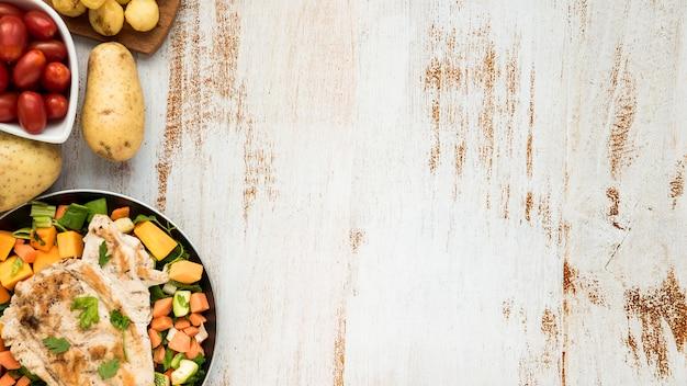 Kip op bakplaat en groenten op grunge geschilderd bureau Gratis Foto