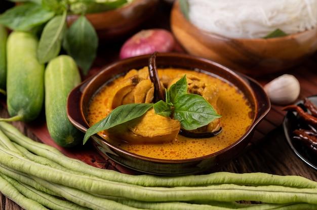 Kip rode curry in een kom met gedroogde pepers, basilicum, komkommer en kousenband Gratis Foto