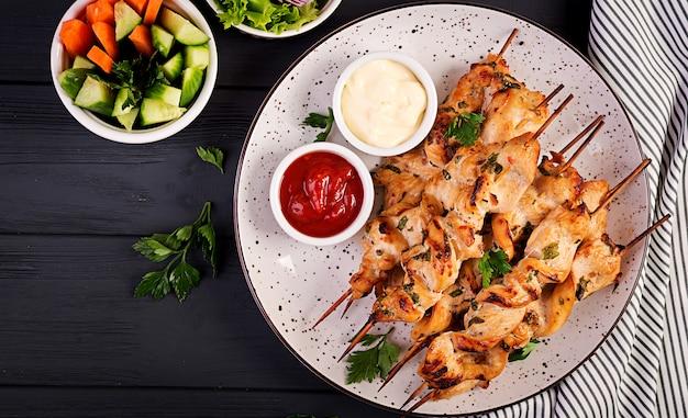 Kip shish kebab. sjasliek - gegrild vlees en verse groenten. bovenaanzicht Premium Foto