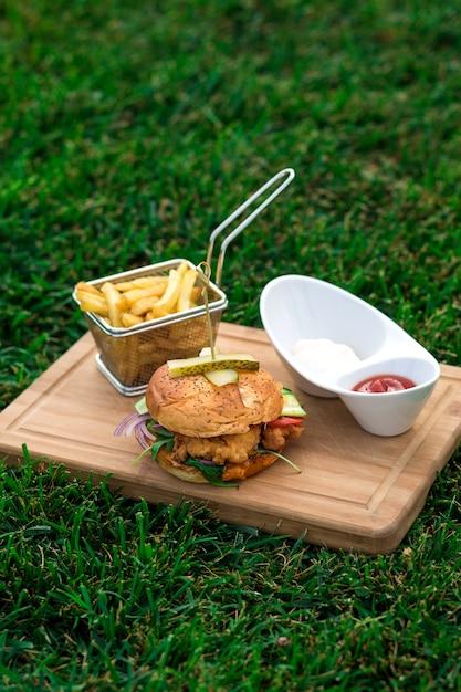 Kipburger geserveerd met frietmand, kom mayonaise en ketchup Gratis Foto