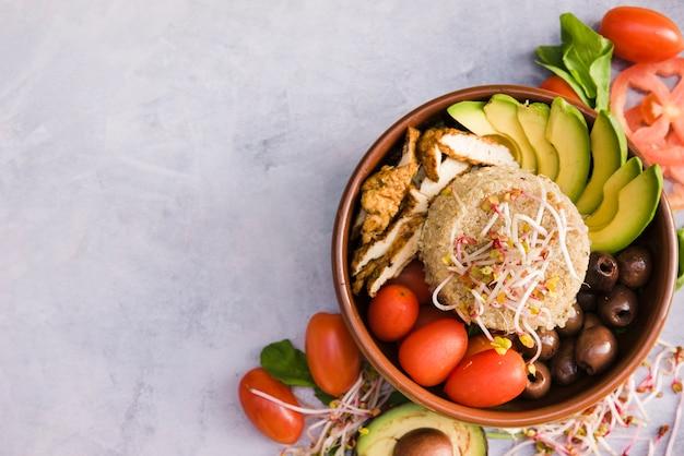 Kipburritokom met rijst; spruit; tomaat; avocado en olijven op concrete achtergrond Gratis Foto