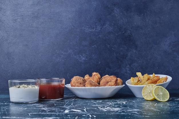 Kipnuggets met aardappelen en sauzen in witte borden. Gratis Foto