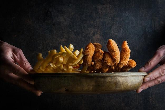 Kipnuggets met frietjes en menselijke hand in kleigerechten Gratis Foto