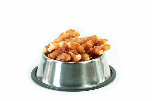 Kippenbeen in roestvrije kom voor geïsoleerde hond. snack voor huisdieren concept. Premium Foto