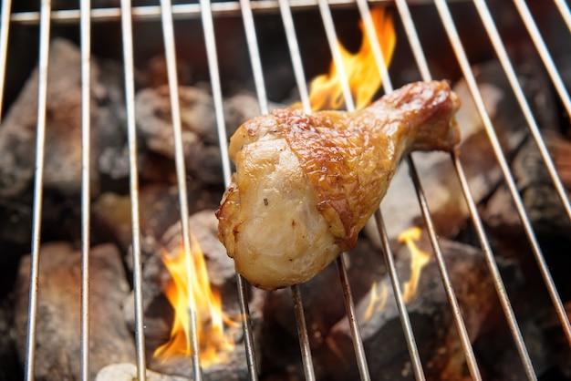 Kippenbenen die over vlammen op een barbecue roosteren. Premium Foto