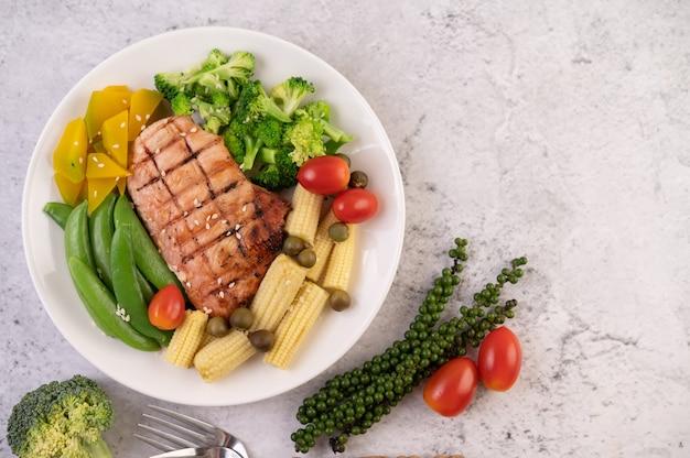 Kippenbiefstuk gegarneerd met witte sesam, erwten, tomaten, broccoli en pompoen in een witte plaat. Gratis Foto