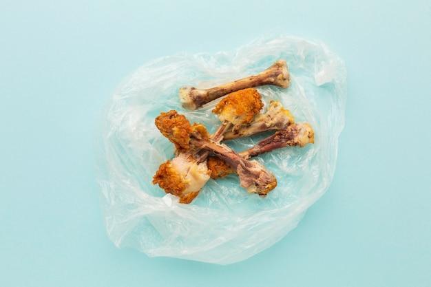 Kippenboutjes restjes in een plastic zak Gratis Foto