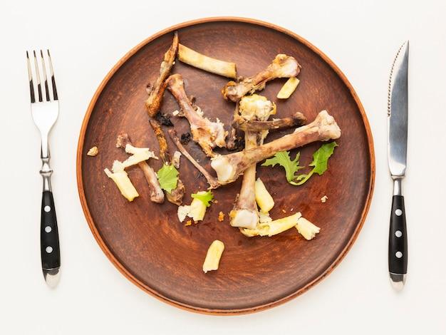 Kippendrumsticks overgebleven botten in een bord Premium Foto