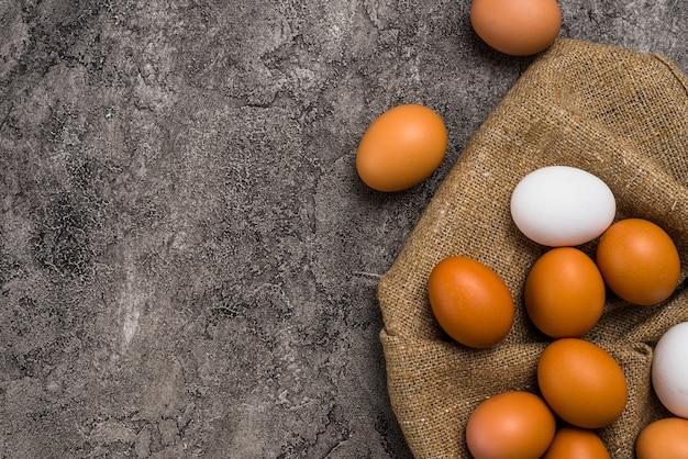 Kippeneieren die op bruin canvas worden verspreid Gratis Foto