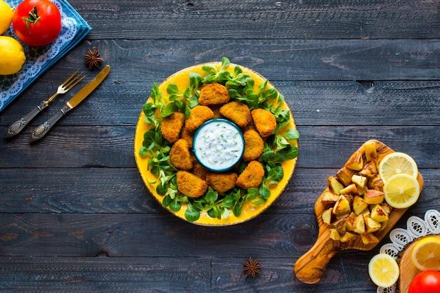 Kippengoudklompjes met yoghurtsaus op een houten achtergrond Premium Foto