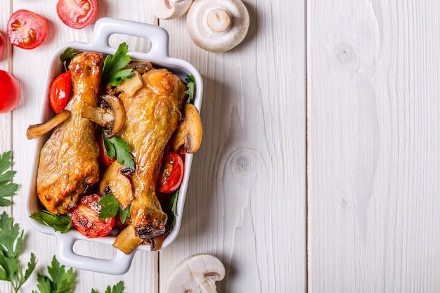 Kippenpoten gebakken met champignons en tomaten Premium Foto