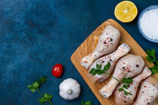 Kippenpoten met kruiden en zout klaar voor het koken op snijplank. Premium Foto