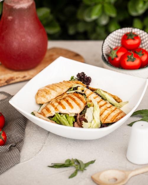 Kippensalade met sla en maïs in witte keramische kom Gratis Foto