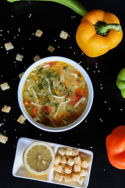 Kippensoep wortel pasta dille tomaat citroen crackers peper bovenaanzicht Gratis Foto
