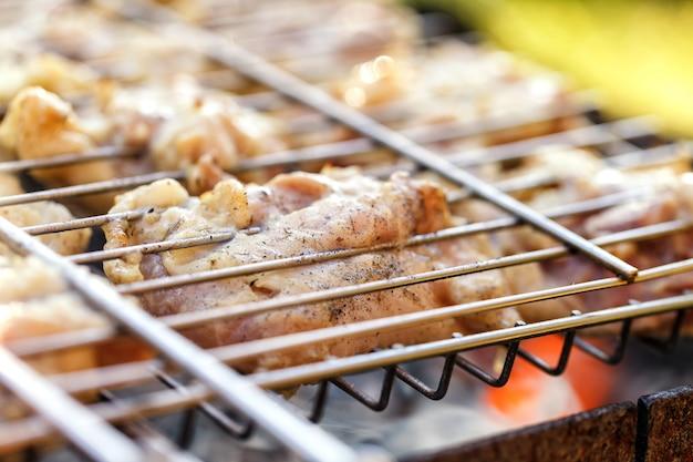 Kippenvlees dat op een barbecuegrill wordt gebraden. Premium Foto
