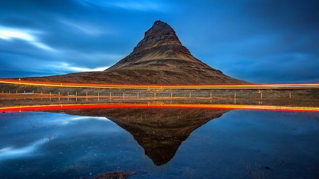 Kirkjufell-bergen en bezinning met autolicht, ijsland. Gratis Foto