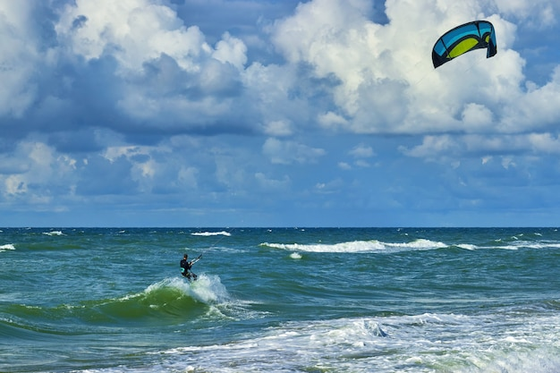 Kitesurfer op de top van een golf. blauwe lucht met witte wolken en turquoise zee Premium Foto