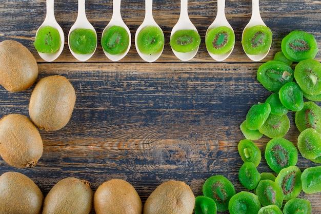 Kiwi met gedroogde plakjes plat lag op een houten achtergrond Gratis Foto