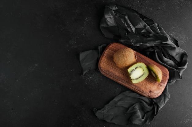Kiwies op een houten bord op het tafellaken, bovenaanzicht. Gratis Foto