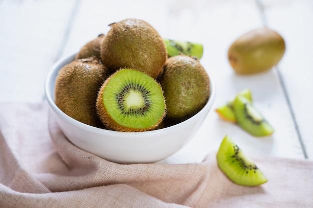 Kiwifruit op witte houten lijst, tropisch fruit Premium Foto