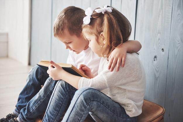 Klaar voor grote reizen. gelukkig meisje en jongenslezing intereting boek die een grote aktentas en het glimlachen dragen. reizen, vrijheid en verbeelding Premium Foto