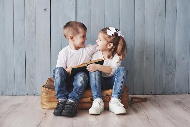 Klaar voor grote reizen. gelukkige meisje en jongen die interessant boek lezen die een grote aktentas en het glimlachen dragen. reizen, vrijheid en verbeelding Premium Foto