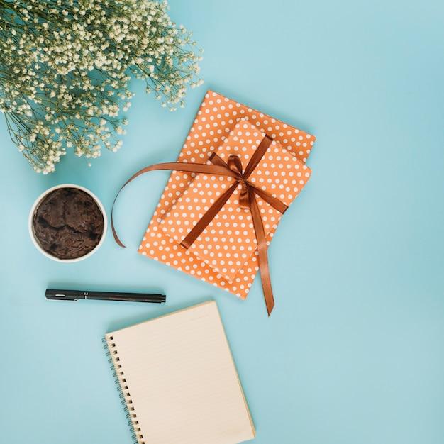 Kladblok en cadeau in de buurt van cupcake en boeket Gratis Foto