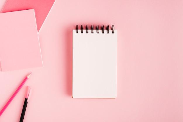 Kladblok en kantoorbenodigdheden op gekleurd oppervlak Gratis Foto