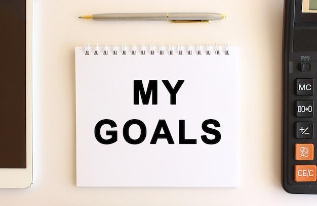 Kladblok met tekst mijn doelen op een witte achtergrond, in de buurt van rekenmachine, tablet en pen. bedrijfsconcept. Premium Foto