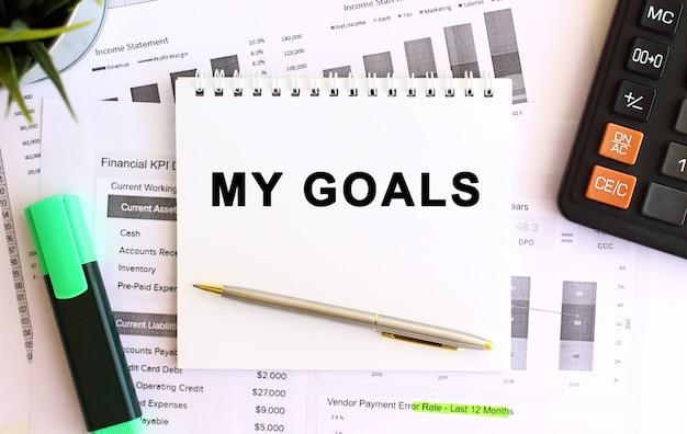Kladblok met tekst my goals op een witte achtergrond, in de buurt van rekenmachine en kantoorbenodigdheden. bedrijfsconcept. Premium Foto