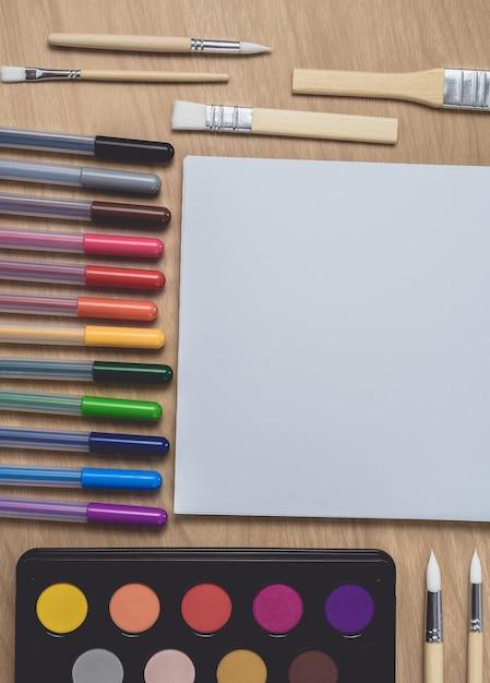 Kladblok met veel kleurrijke pennen en penseel op bruine houten tafel Premium Foto
