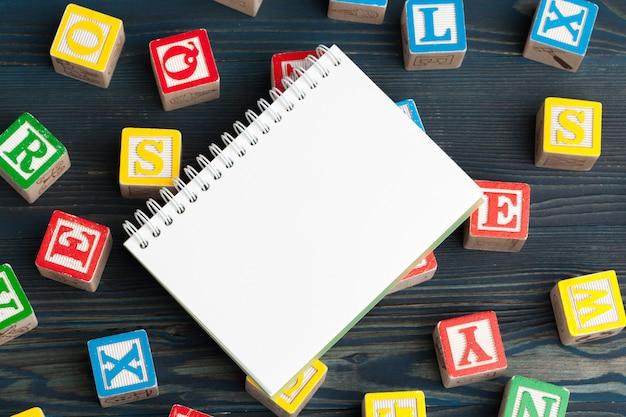 Kladblok op houten tafel en houten alfabet blokken Premium Foto