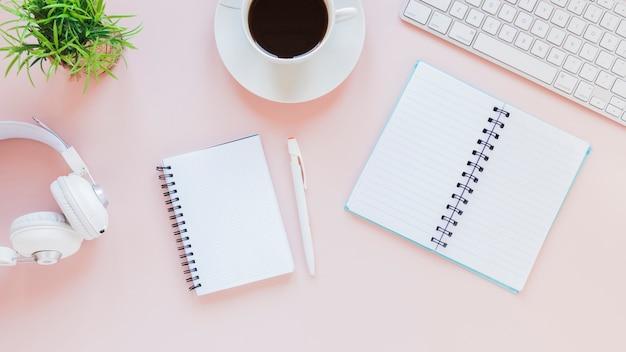 Kladblokken en koffiekopje in de buurt van hoofdtelefoons en toetsenbord Gratis Foto