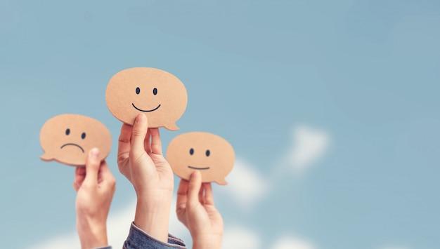 Klant die classificatie met gelukkig pictogram op hemelachtergrond tonen, het onderzoekconcept van de klanttevredenheid, exemplaarruimte. Premium Foto