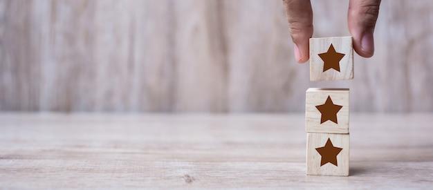 Klant die houten blokken met het drie sterrensymbool houdt. Premium Foto