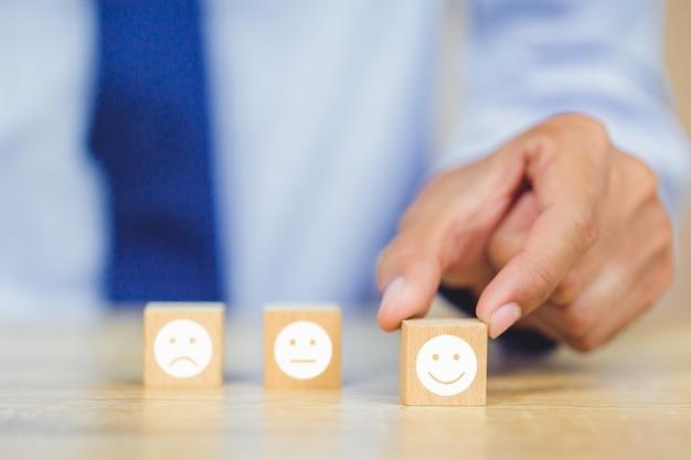 Klant die smileygezicht emoticon op houten kubus drukken Premium Foto
