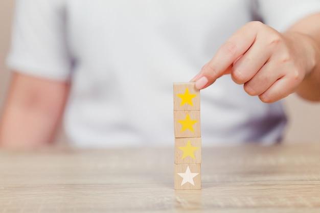 Klant die ster op houten kubus drukt Premium Foto