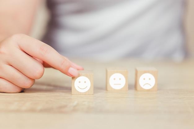 Klant het drukken smileygezicht emoticon op houten kubus. Premium Foto